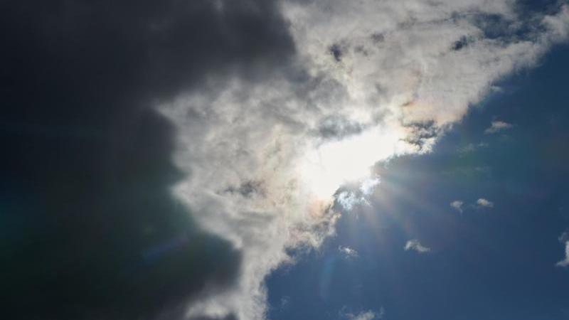 Die Sonne scheint durch eine Wolkendecke hindurch. Foto: Annette Riedl/dpa/Symbolbild