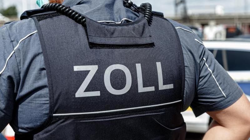 """Ein Beamter trägt während seines Dienstes eine Schutzweste mit der Aufschrift """"Zoll"""". Foto: Markus Scholz/dpa/Symbolbild"""