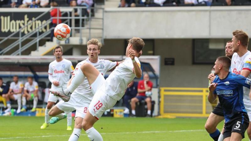 Kiels Torschütze Joshua Mees (2.v.l.) setzt sich durch und erzielt den Treffer zum 1:2. Foto: Friso Gentsch/dpa