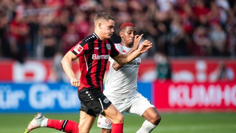 Leverkusens Florian Wirtz (l) und der Mainzer Leandro Barreiro kämpfen um den Ball. Foto: Marius Becker/dpa