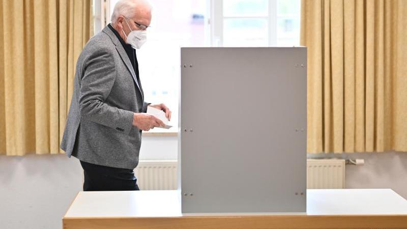 Winfried Kretschmann geht zur Wahlkabine, um danach seinen Stimmzettel in die Wahlurne einzuwerfen. Foto: Felix Kästle/dpa