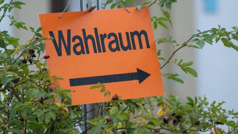 """Ein Schild mit der Aufschrift """"Wahlraum"""" zeigt den Weg zu einem Wahllokal. Foto: Harald Tittel/dpa"""