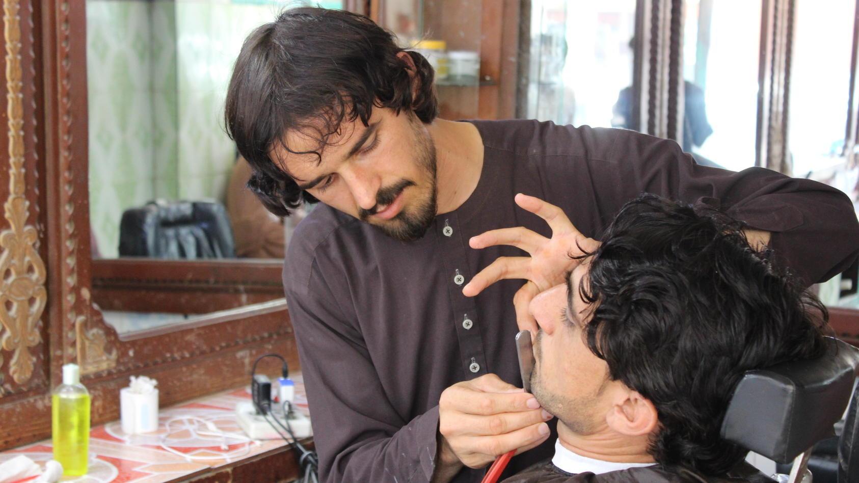 Ein afghanischer Friseur rasiert einem Kunden den Bart. Die Terror-Herrschaft der Taliban verbietet künftig einen individuellen Look.