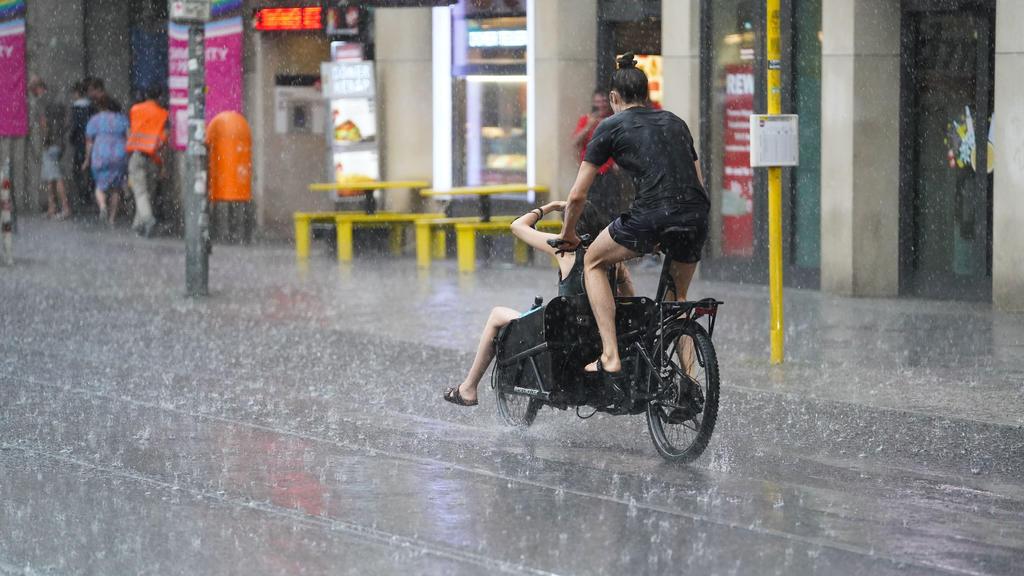 25.07.2021, Berlin: Junge Leute fahren mit einem Lastenfahrrad, während starker Regen auf die Straße prasselt.