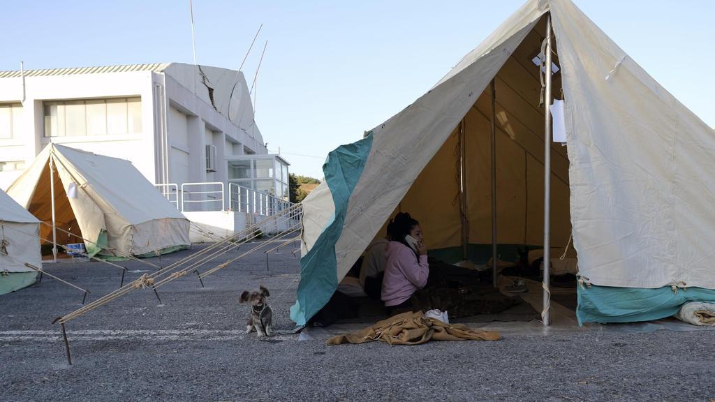 28.09.2021, Griechenland, Arkalochori: Eine Frau telefoniert mit ihrem Handy, während ein Hund vor einem Zelt im Dorf Arkalochori auf der südlichen Insel Kreta steht. Erneut hat ein Beben am Dienstagmorgen die Mittelmeerinsel Kreta erschüttert. Foto: