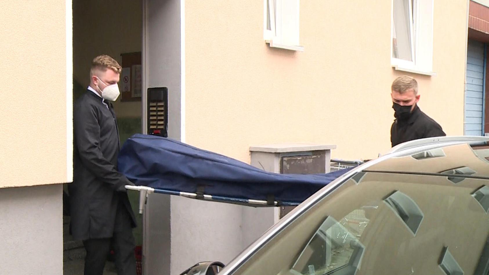 Zwei Männer tragen die Leiche der 53-Jährigen aus ihrem Wohnhaus.