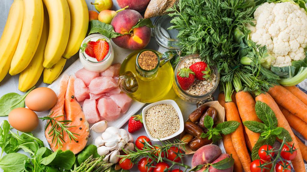 Verschiedene Obst- und Gemüstesorten liegen auf einem Tisch, sowie frischer Fisch etc.