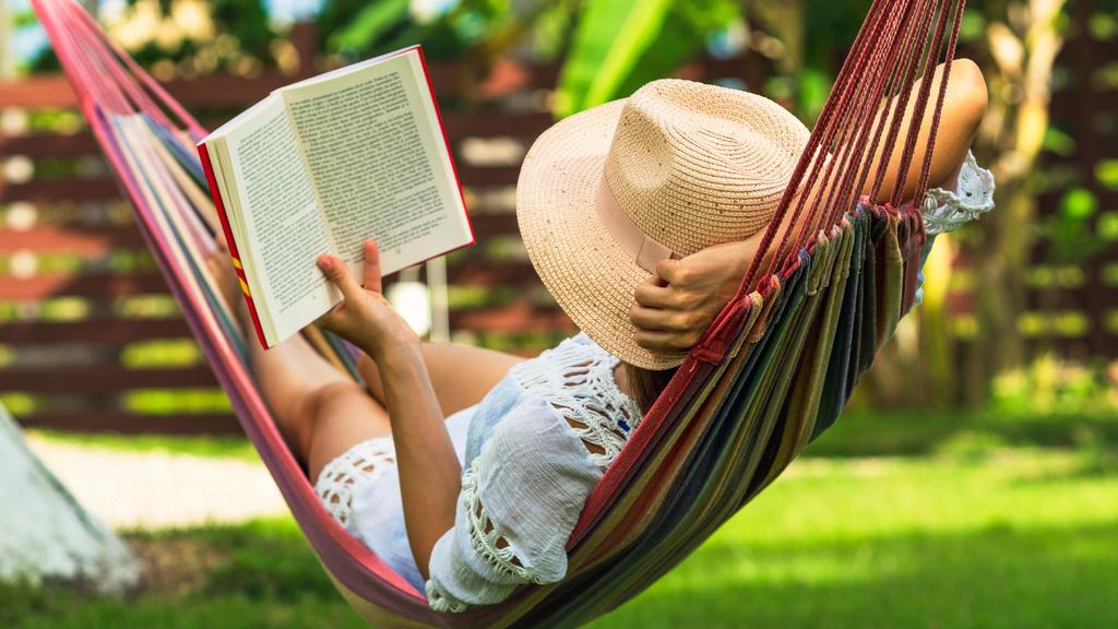 Eine Frau spannt auf einer Hängematte im Garten aus und liest ein Buch.