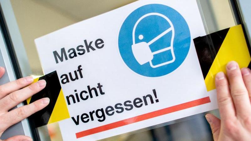 """""""Maske auf nicht vergessen!"""" - In einigen Schulen können diese Schilder wohl bald abgehangen werden."""