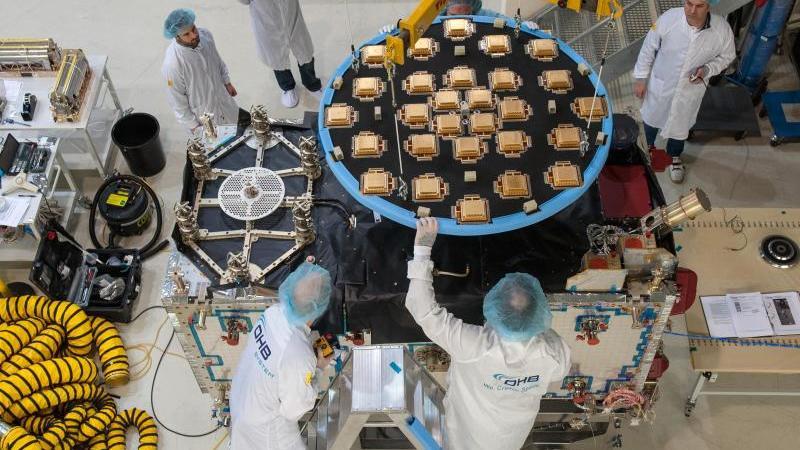 Im Reinraum des Raumfahrtunternehmens OHB System in Bremen montieren Techniker die kreisrunde Antenne auf einen Satelliten. Foto: Ingo Wagner/dpa/Archivbild