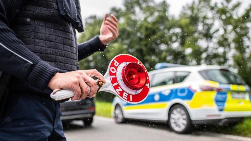 Eine Polizistin hält eine Winkerkelle in der Hand. Foto: Guido Kirchner/dpa/Symbolbild