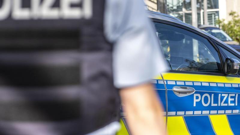 Ein Polizist steht vor einem Streifenwagen. Foto: David Inderlied/dpa/Illustration