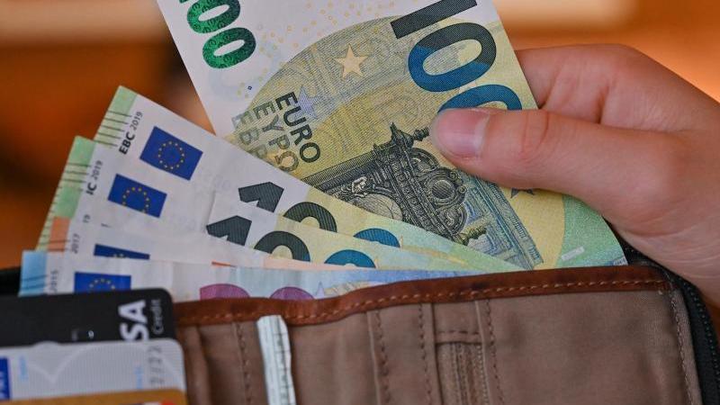 Eine Frau nimmt einen Geldschein aus einem Portemonnaie. Foto: Patrick Pleul/dpa-Zentralbild/dpa/Illustration