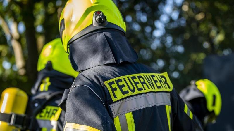 Einsatzkräfte der Feuerwehr stehen beieinander. Foto: David Inderlied/dpa/Symbolbild