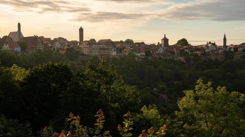 Die flach stehende Morgensonne lässt das Taubertal und die Stadtsilhouette in einem goldenen Licht erstrahlen. Foto: Nicolas Armer/dpa/Archivbild