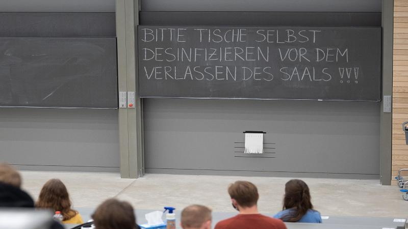 Studierende mit Mund- und Nasenmaske sitzen in einem Hörsaal. Foto: Sebastian Gollnow/dpa/Symbolbild
