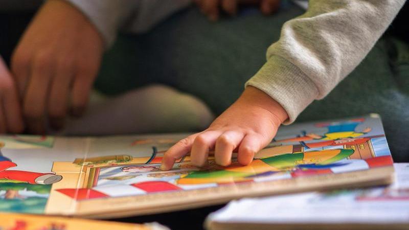 Eine Praktikantin liest in einer Kita Kindern vor. Foto: Sebastian Gollnow/dpa/Illustration