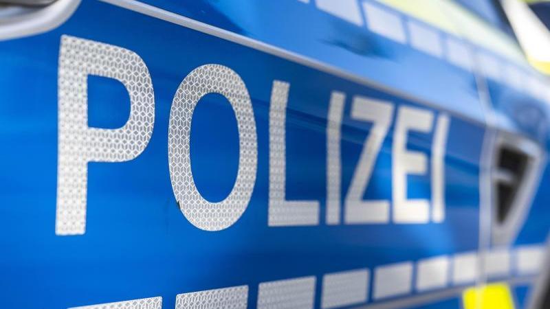 """An der Tür von einem Streifenwagen steht der Schriftzug """"Polizei"""". Foto: David Inderlied/dpa/Illustration"""