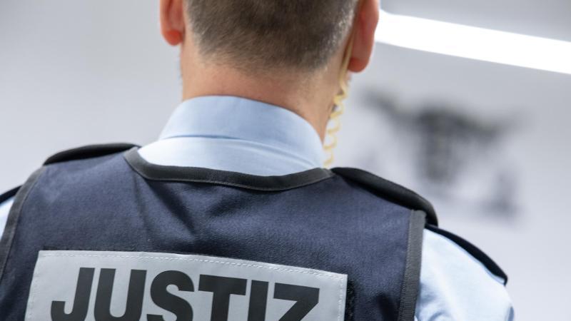 Ein Justizbeamter steht in einem Gerichtssaal. Foto: Sebastian Gollnow/dpa/Symbolbild
