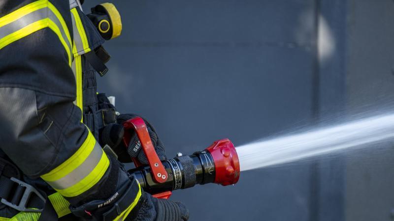 Ein Mitglied der Feuerwehr spritzt aus einem Schlauch mit Wasser. Foto: David Inderlied/dpa/Symbolbild