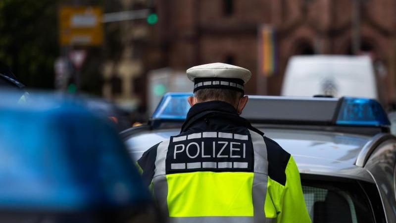 Ein Polizeibeamter steht zwischen zwei Einsatzfahrzeugen der Polizei. Foto: Philipp von Ditfurth/dpa/Symbolbild