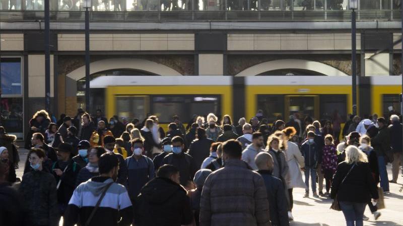 Menschen gehen auf dem Alexanderplatz. Foto: Carsten Koall/dpa/Symbolbild
