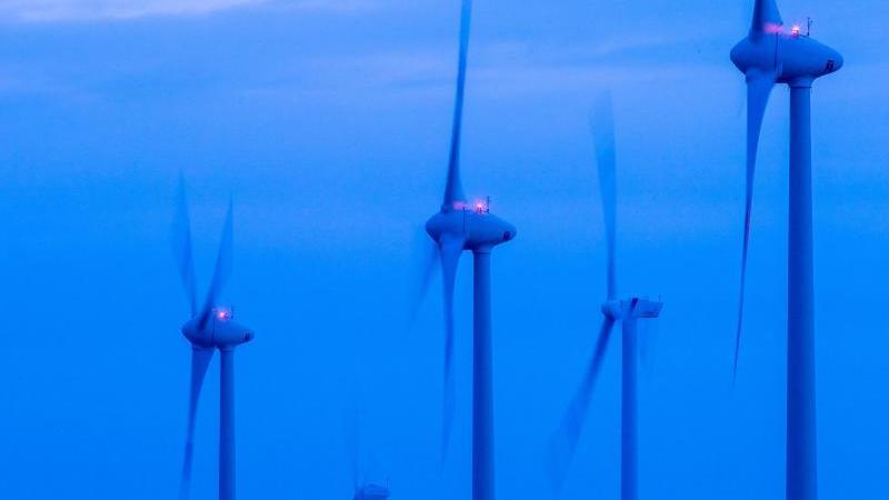 Windkraftanlagen drehen sich vor Sonnenaufgang in einem Windpark. Foto: Jens Büttner/dpa/Archivbild