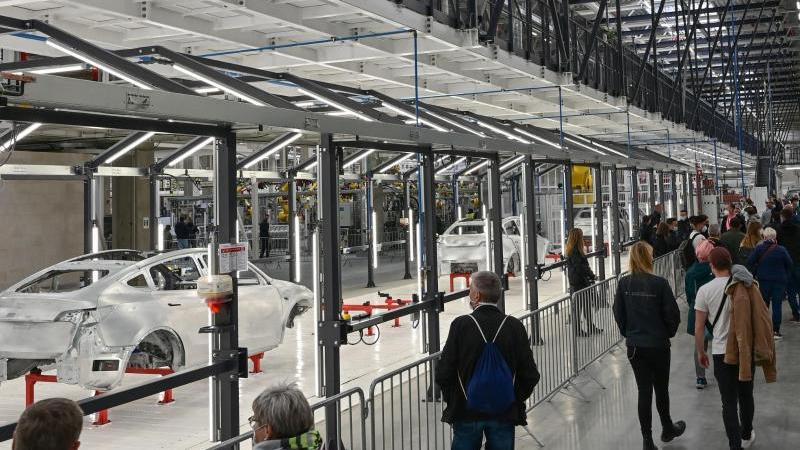 Besucherinnen und Besucher gehen am Tag der offenen Tür durch eine Fabrikhalle der Tesla Gigafactory. Foto: Patrick Pleul/dpa-Zentralbild/dpa