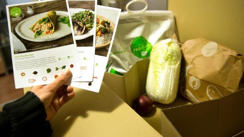 Ein Mann hält mitgelieferte Kochrezepte aus einer HelloFresh Kochbox in der Hand. Foto: picture alliance/dpa/Symbolbild