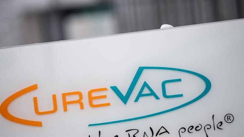 """Das Logo des Biotech-Unternehmen Curevac mit dem Slogan """"the RNA people"""" steht an einer Tür. Foto: Sebastian Gollnow/dpa/Symbolbild"""