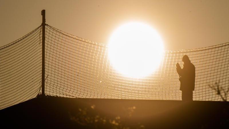 ein-bauarbeiter-steht-bei-sonnenaufgang-auf-einer-baustelle-auf-dem-dach-foto-julian-stratenschultedpasymbolbild