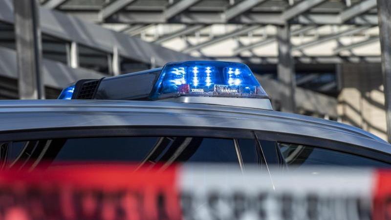 ein-polizei-blaulicht-leuchtet-uber-einem-absperrband-mit-der-aufschrift-polizeiabsperrung-foto-david-inderlieddpaillustration