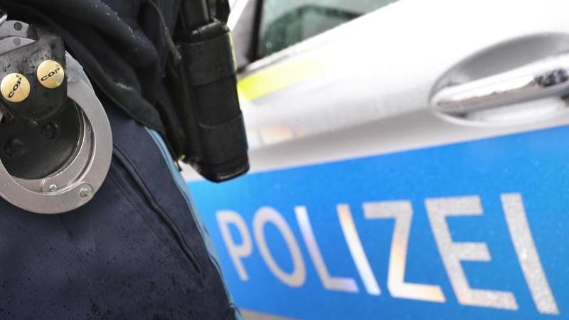 ein-polizist-mit-handschellen-und-einer-pistole-am-gurtel-steht-vor-einem-streifenwagen-foto-karl-josef-hildenbranddpa