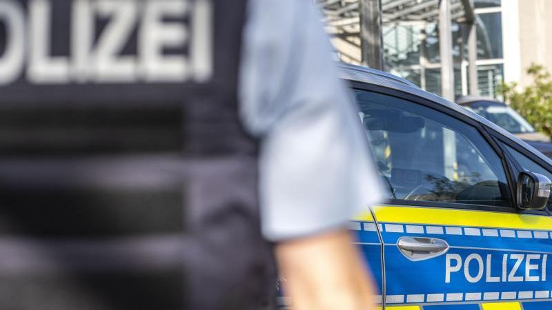 ein-polizist-steht-vor-einem-streifenwagen-foto-david-inderlieddpasymbolbild
