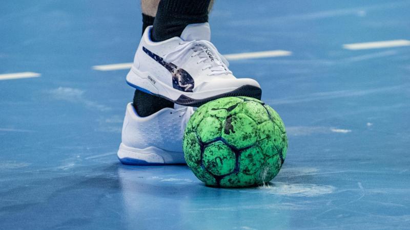 ein-spieler-halt-einen-handball-mit-dem-fu-fest-foto-andreas-goradpasymbolbild