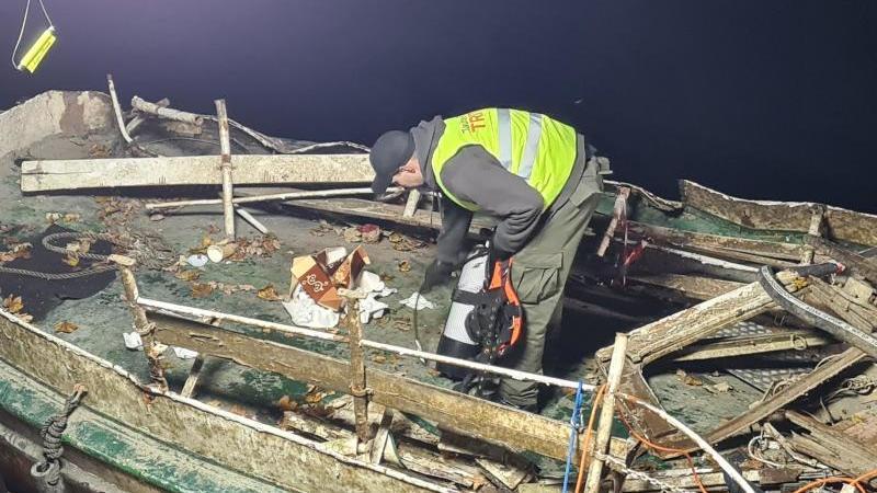 ein-mann-steht-auf-dem-versunkenen-und-wieder-aufgetauchten-fahrgastschiff-moornixe-foto-markus-gaykdpa