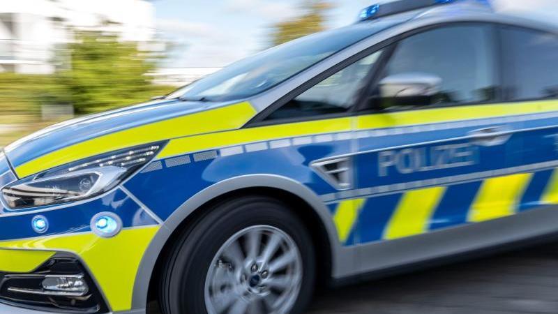 ein-polizeiwagen-fahrt-mit-eingeschaltetem-blaulicht-foto-david-inderlieddpaillustration