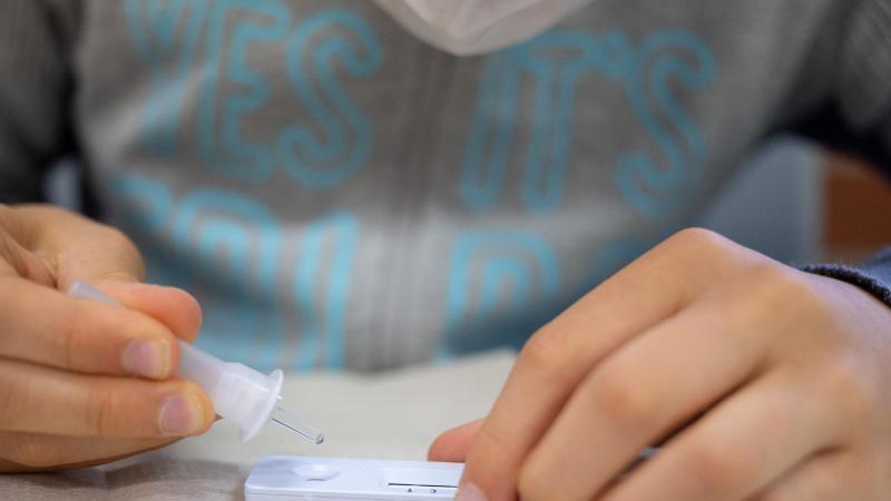 ein-schuler-macht-vor-der-ersten-stunde-an-einer-schule-einen-corona-schnelltest-foto-sebastian-gollnowdpaillustration