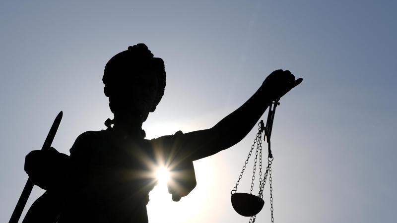 eine-statue-der-justitia-mit-einer-waage-und-einem-schwert-in-ihren-handen-foto-arne-dedertdpasymbolbild