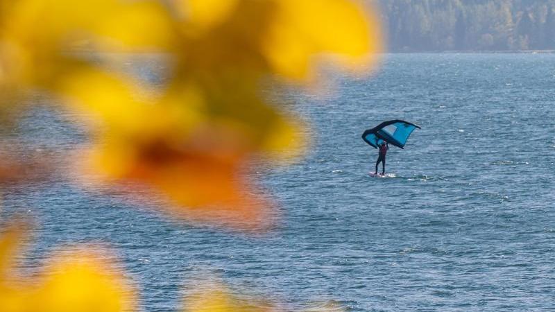 ein-windsurfer-gleitet-mit-seinem-freizeitsportgerat-uber-das-wasser-foto-peter-kneffeldpaarchivbild
