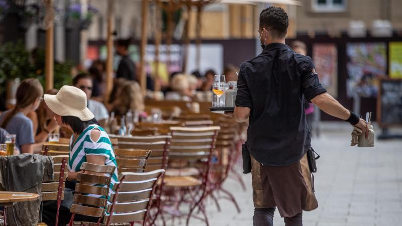 eine-servicekraft-lauft-im-auenbereich-eines-restaurants-an-gasten-vorbei-foto-christoph-schmidtdpaarchivbild
