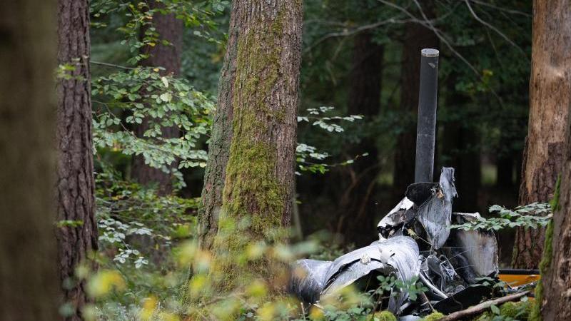 trummerteile-eines-hubschraubers-vom-typ-robinson-r44-und-feuerloscher-liegen-in-einem-wald-nahe-der-grenze-zu-hessen-und-bayern-foto-sebastian-gollnowdpaarchivbild