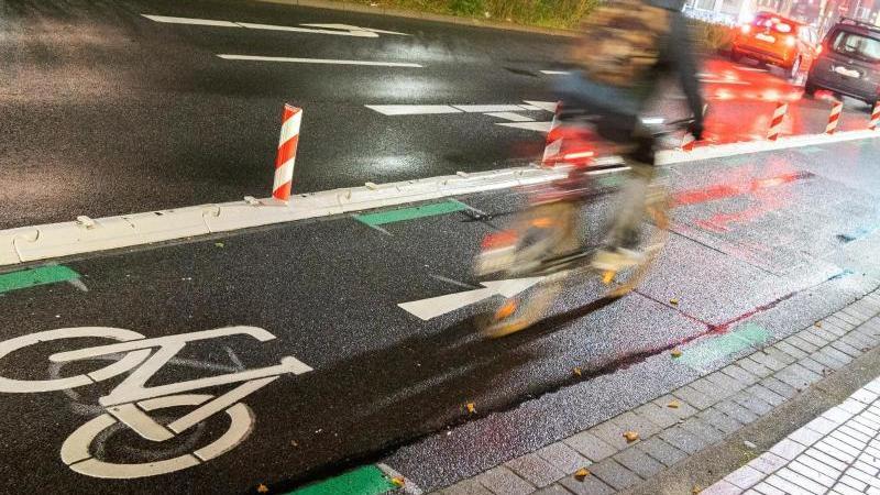 ein-mann-fahrt-mit-einem-fahrrad-am-fruhen-morgen-uber-die-veloroute-in-die-innenstadt-foto-julian-stratenschultedpaarchivbild