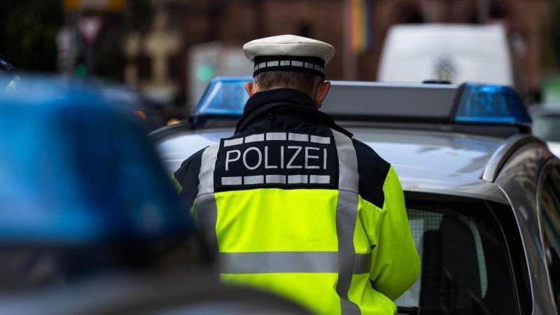 ein-polizeibeamter-steht-zwischen-zwei-einsatzfahrzeugen-foto-philipp-von-ditfurthdpasymbolbild