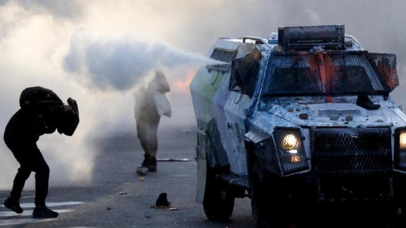 demonstranten-rennen-als-die-polizei-wasserwerfer-einsetzt-zwei-jahre-nach-beginn-der-heftigen-proteste-gegen-die-konservative-regierung-sind-in-chile-erneut-tausende-menschen-auf-die-strae-gegangen-foto-uncreditedapdpa