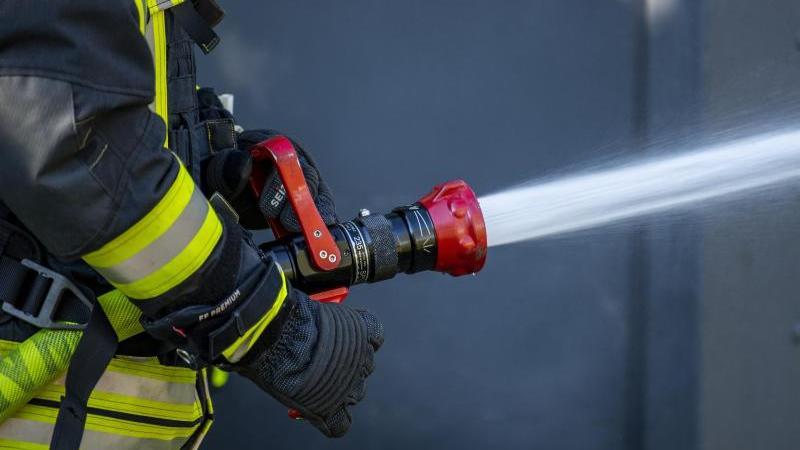 ein-mitglied-der-feuerwehr-spritzt-aus-einem-schlauch-mit-wasser-foto-david-inderlieddpasymbolbild