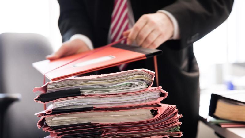 ein-staatsanwalt-steht-vor-einem-stapel-gerichtsakten-foto-christian-charisiusdpasymbolbild