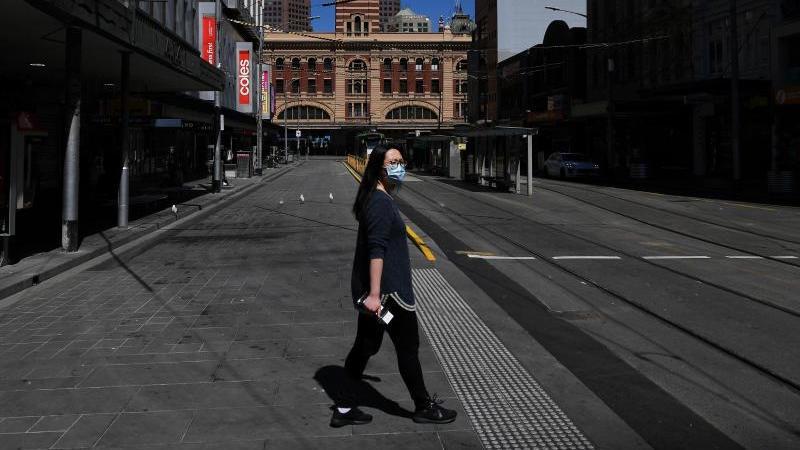 eine-person-mit-gesichtsmaske-geht-uber-die-strae-in-melbourne-foto-james-rossaapdpa