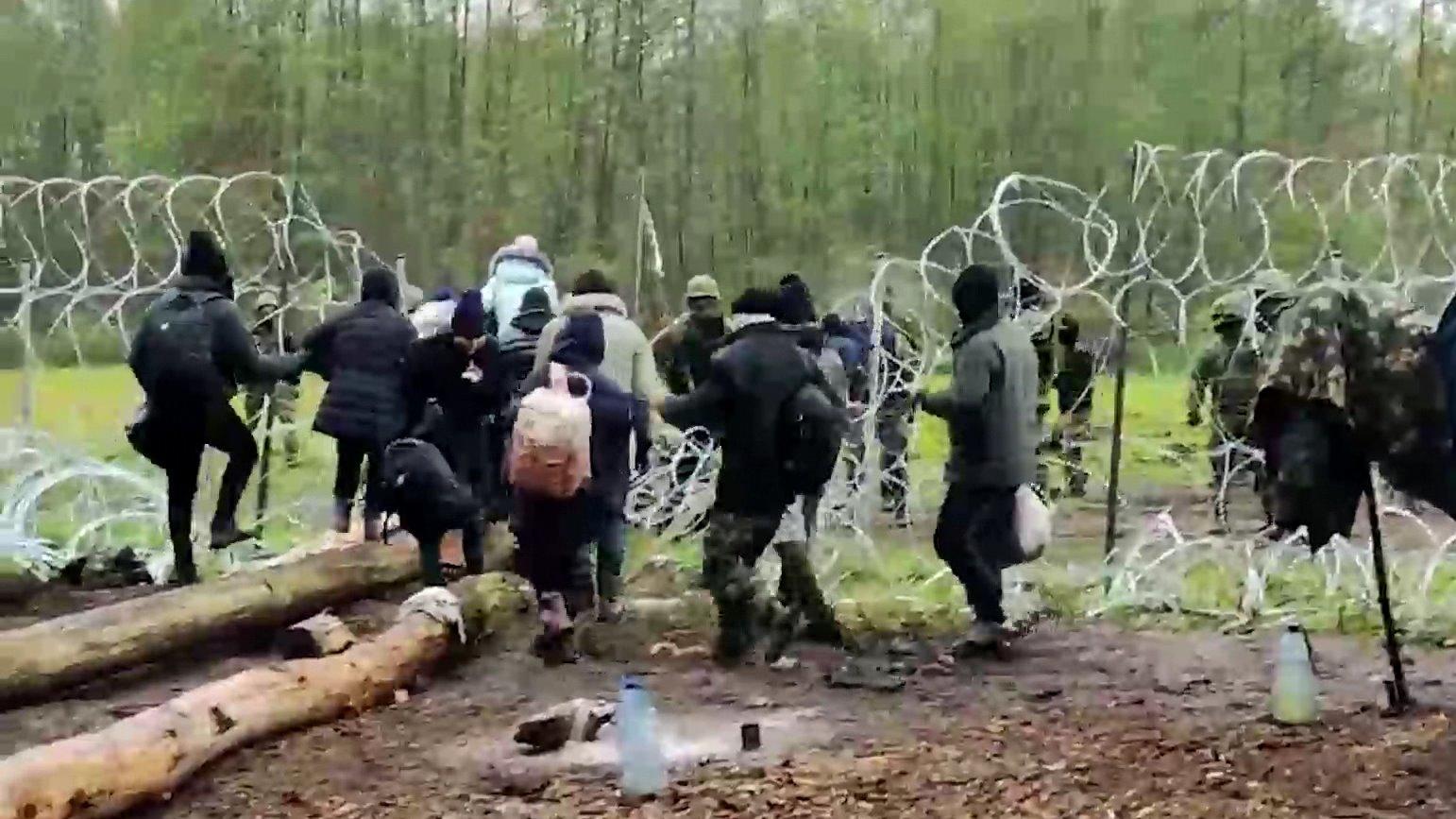 eine-an-der-polnisch-belarussischen-grenze-festsitzende-gruppe-von-migranten-versucht-die-grenzbarriere-zu-durchbrechen