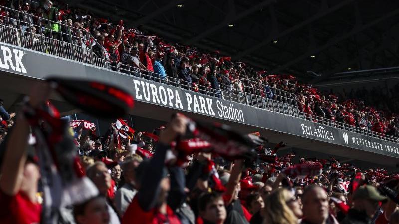 fans-stehen-vor-einem-spiel-auf-der-tribune-des-neuen-europa-park-stadions-foto-tom-wellerdpa